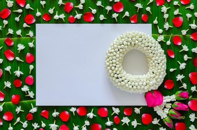 ソンクラン祭りのバナナの葉の背景にジャスミンの花輪と花と白い白紙。