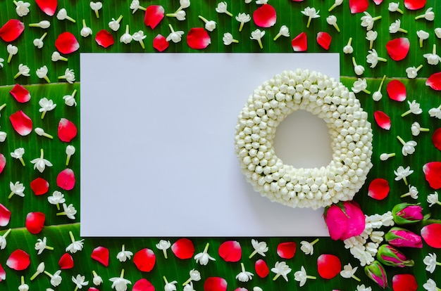 White blank paper with jasmine garland and flowers on banana leaf background for songkran festival.