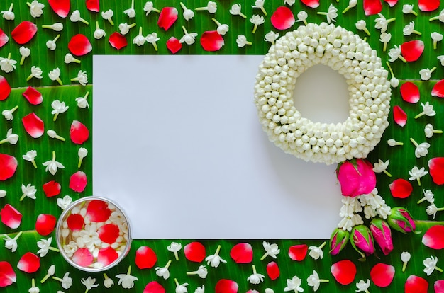 White blank paper with jasmine garland and flowers in water bowl on banana leaf background for songkran festival.