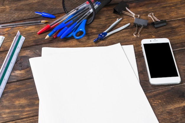 White blank paper with stationeries and smartphone on wooden table