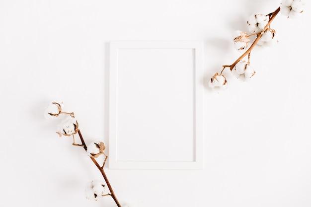 白い空白のフォト フレームのモックアップと綿の枝。フラットレイ、トップビュー