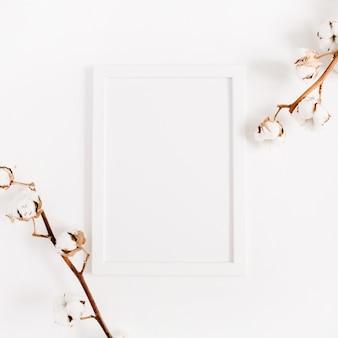 白い空白のフォト フレームのモックアップと綿の枝。平置き