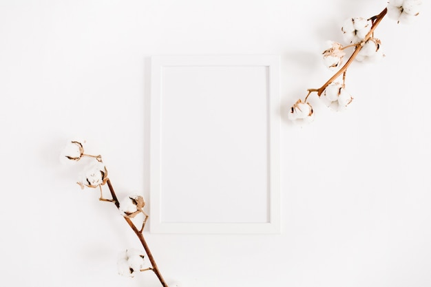 白い空白のフォトフレームのモックアップと白の綿の枝