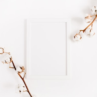 White blank photo frame mock up and cotton branches. flat lay