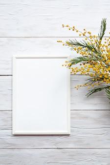 Белая пустая фоторамка с букетом мимозы на белом деревянном столе