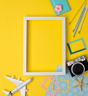White blank photo frame with camera, plane, starfish, pencils