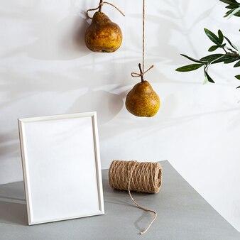 Белая пустая фоторамка с грушами и тенями оливковой ветви
