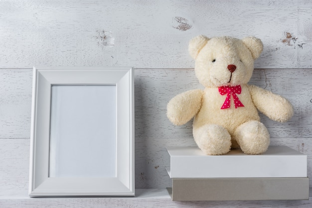 White blank photo frame on wooden shelf and wall, decorate with stack of books and teddy bear doll