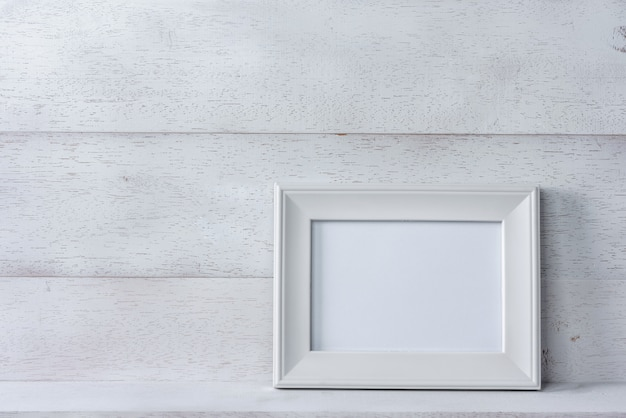 White blank photo frame on wooden shelf and wall