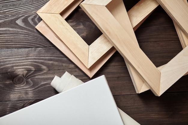 Белая пустая картина и рулон холста с подрамниками на коричневом деревянном столе