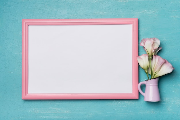 White blank picture frame with pink border and vase on blue background