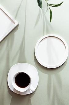 Белые пустые круглые и квадратные фоторамки и белая чашка черного кофе