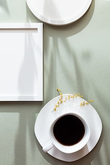 White blank round and square photo frames and white cup of black coffee