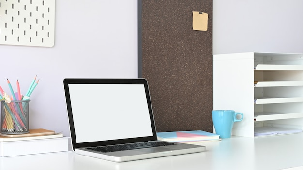 A white blank screen computer laptop is putting on a white working desk surrounded by office equipment.