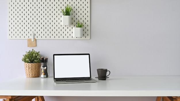 A white blank screen computer laptop is putting on a white workspace surrounded by office equipment.