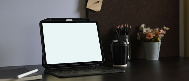 A white blank screen computer tablet is putting on a working desk surrounded by various equipment.