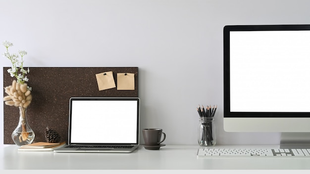 A white blank screen laptop is putting on a white working desk surrounded by office equipment.