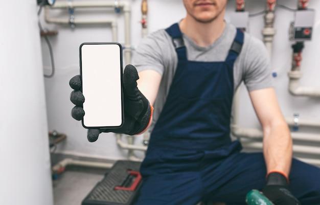 保護手袋で配管工の手に白い空白の画面の携帯電話