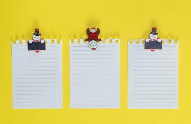 White blank sheet in a line torn out of notepad on a yellow background
