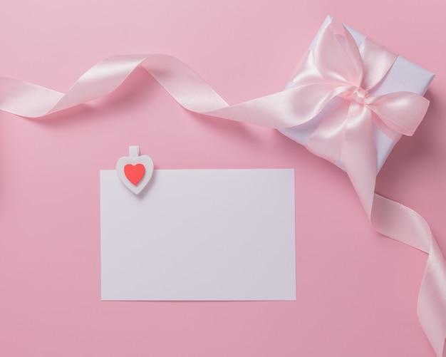 Белый чистый лист бумаги и подарочная коробка на розовом фоне. концепция дня святого валентина.