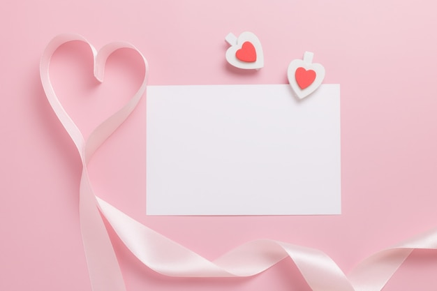 White blank sheet of paper and pink ribbon in the shape of a heart on a pink background. valentine's day concept.