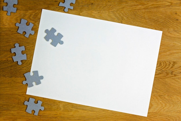 White blank sheet of paper surrounded by puzzle pieces on wooden background top view copy space for ...