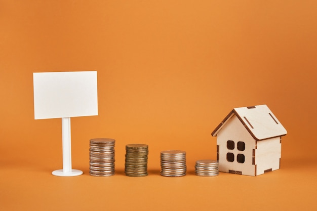 White blank sign, house model and towers of coins on a brown background