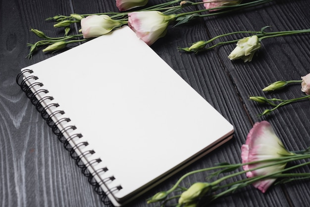 White blank spiral notepad with purple eustoma flowers over the wooden desk