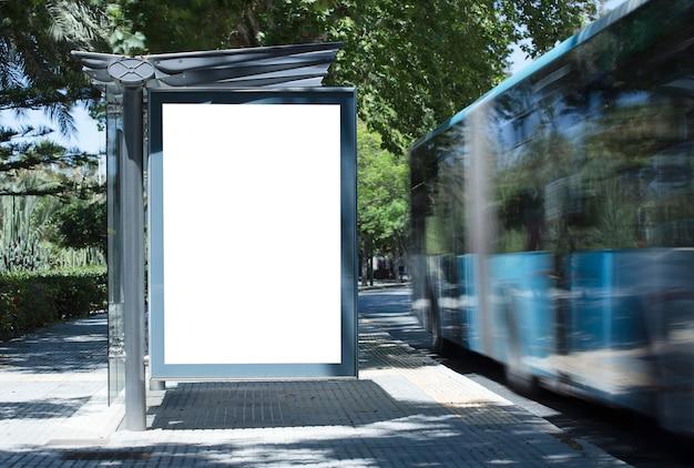 Белый пустой вертикальный рекламный щит на автобусной остановке на городской улице на фоне автобусов и ро