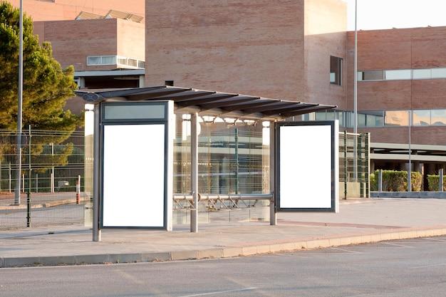 Белый пустой вертикальный рекламный щит на автобусной остановке на городской улице знак на улице рядом с