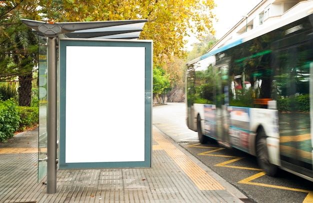 White blank vertical billboard at the bus stop on the city street