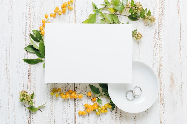 White blank wedding card with flowers; yellow berries and wedding rings on wooden backdrop
