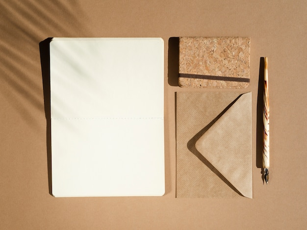White blank with beige pen on a beige background with a palm leaf shadow