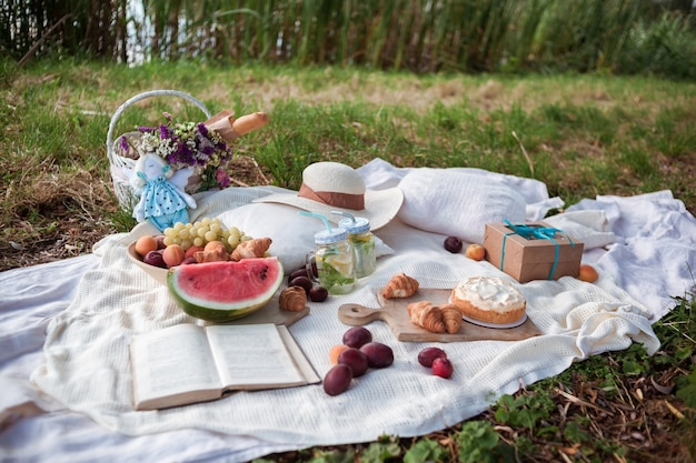 White blanket with fruits and pastries, lemonade, opened books, straw hat, gift box, white basket with flowers and baguette on picnic in a city park.
