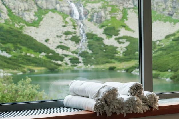 Белые одеяла лежат на подоконнике перед прекрасным видом на озеро, водопад и