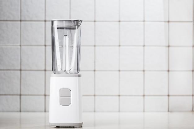 White blender on the table with light kitchen tiles