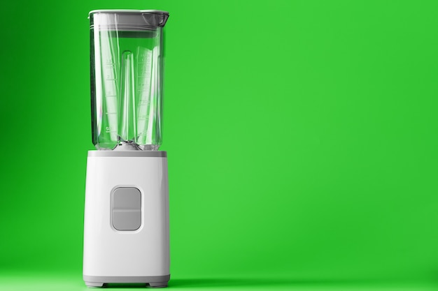 A white blender with an empty glass on a green surface