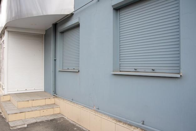 店の閉店として、ドアの白いブラインドと窓の灰色。小売危機の概念。閉店