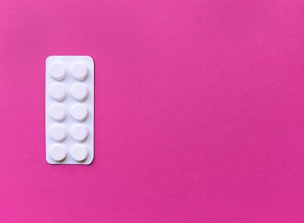 Белый блистер таблеток на розовом фоне. простая плоская планировка с пастельной текстурой с копией пространства. медицинская концепция.
