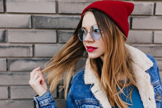 트렌디 한 화장과 흰색 금발 소녀 장난스럽게 도시 거리에 포즈. 야외 시간을 보내는 데님 재킷에 잘 생긴 젊은 여자의 초상화.