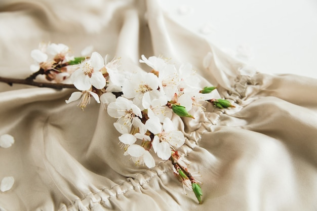 White blossom flowers on beige silk fabric clothes on white background