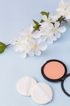 White blossoms; two sponges and blusher on blue background