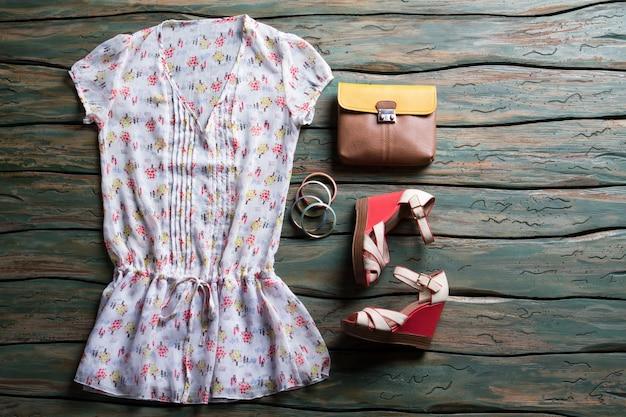 白いブラウスとウェッジサンダル。二色の茶色の財布とブレスレット。緑の木製の棚の服。スタイリッシュな靴を履いた女性の衣装。