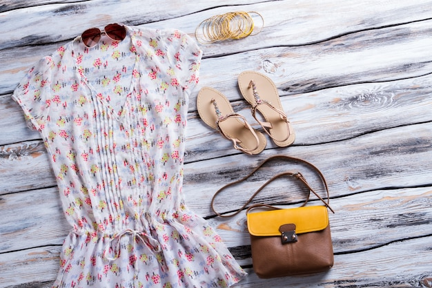White blouse with colorful pattern. blouse, sandals and bicolor purse. lady's leather bag on sale. new accessories at fashion store.