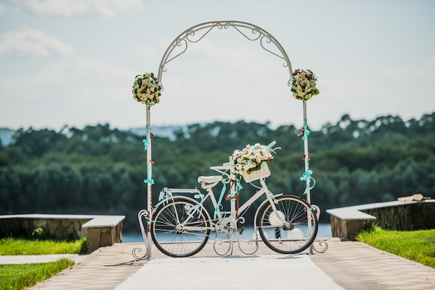 White and blue arch decorated with flowers bycicle, wedding registration outdoors