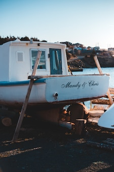White and blue boat on brown wooden dock during daytime