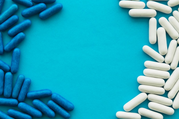 White and blue candy capsules forming frame on cyan background