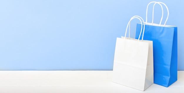 Белые синие крафт бумажные пакеты. пакеты хозяйственных сумок бумажные на белой предпосылке таблицы голубой светлой с космосом экземпляра. покупки, продажа, доставка еды. длинный веб-баннер копией пространства