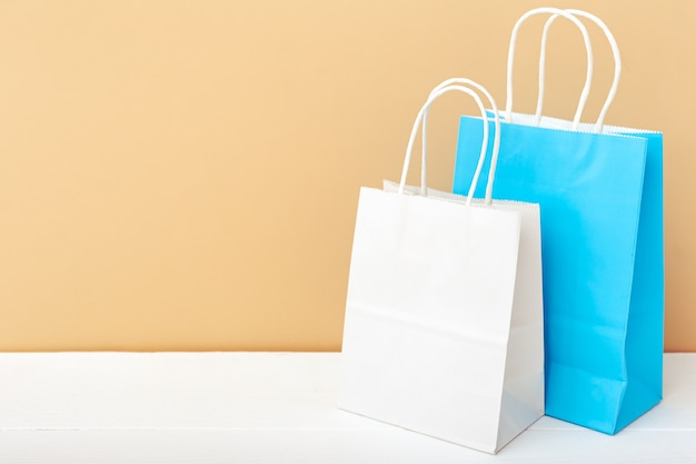 ホワイトブルーのクラフト紙袋。ショッピングモックアップは、白いテーブルベージュのコピースペースに紙袋を袋に入れます。