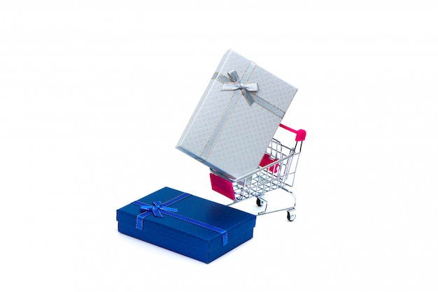 White and blue gift box with ribbon bow and shopping cart or supermarket trolley